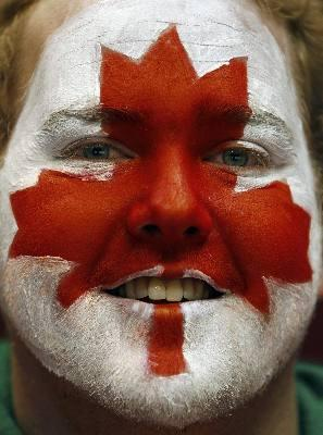 person with a red maple leaf painted on their face