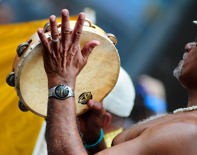 brown set of hands playing a tambourine