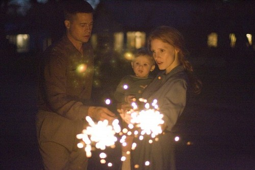 two parents holding a child and sparklers, from The Tree of Life
