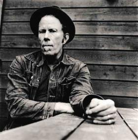 Tom Waits sitting at a picnic table