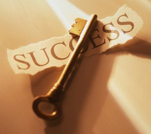 A Key laid over the word Success on a piece of paper